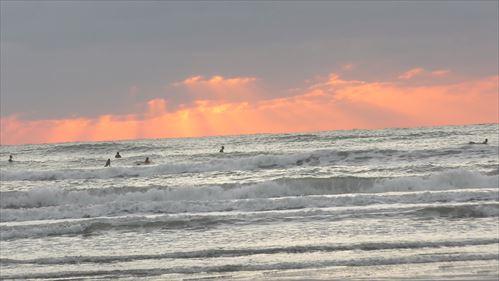 夕陽の中でサーフィン